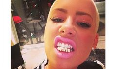 Amber Rose unveils new gold grillz on her teeth
