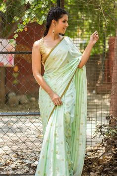 A pastel green marvel, this one is everything a girl needs to satisfy her inner fashionista. Simple yet sultry, a halter neck blouse and red lips will give this saree a complete date night ensemble feel. The muted gold border and the embroidery along the body of the saree glimmers in the sun and makes head turn as you take over the world. ACCOMPANIMENTS: All sarees are sold completely finished with falls (where required) and a free size underskirt. FABRIC: Saree – Cotton satinBorder –…