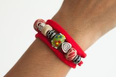 Pulsera realizada con cinta elástica de diferentes colores y abalorios en lava volcánica, plata, cristal de Murano, perlas, coral, resinas teñidas…