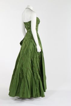 couture green taffeta ball gown, early 1950s. green on ivory woven label, with strapless boned bodice, the dress caught in a spiral of graduated pleats with flounced graduated hem and studded overall with copper and silver facetted beads in varying sizes,