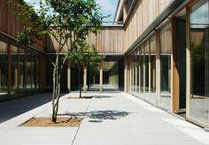 Blick in das Atrium einer Schule mit Holzfassade und grauen WPC Dielen von MYDECK