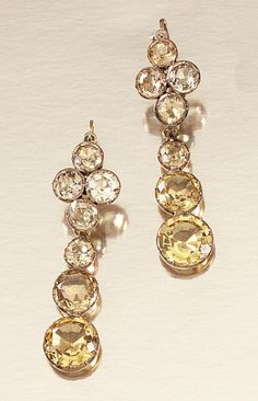 GEM-SET AND DIAMOND JEWELLERY, PORTUGUESE MID 18TH CENTURY AND LATER -  a pair of ear pendants, each surmount composed of a quatrefoil of circular-cut topaz, suspending a graduated trio of similarly-cut topaz of golden tint, original hinged shepherd's crook hook fittings, early 19th century.