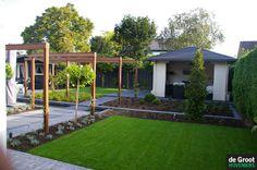 Oplopende tuin met hoogte verschillen gecreëerd door betonbielzen.  In vlakken gaat deze tuin langzaam omhoog.