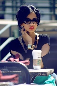 part in the middle, big shades, red lips and a starbucks