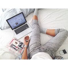 Love everything about this: Comfy bed, grey socks, grey sweatpants, heart-shaped coffee mug, apple laptop, and a Vogue