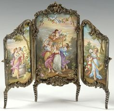 A circa 1890 miniature tri-fold screen with ornate cast rococo style silver frame and Viennese enamel panels.