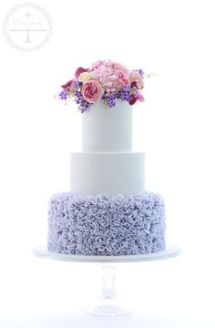 A stunning lavender wedding cake with ruffle detail and fresh blooms from Precious Petals.