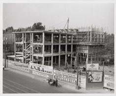 Gemeentelijk zwembad Marnixstraat in aanbouw, reclameteksten op bouwschutting. 1954.