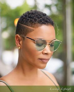 Tapered haircut with a disconnected side part. TWA, black woman.