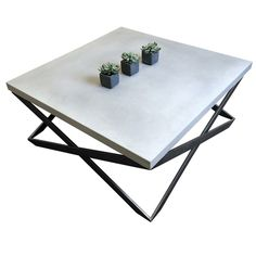 This is a concrete table with a stainless steel cube shaped base.  It can be used as a coffee table, or an end table.