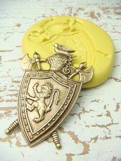 Knights Lion Shield and Battle Axes  - Flexible Silicone Mold - Push Mold, Jewelry Mold, Polymer Clay Mold, Resin Mold, Craft Mold, PMC Mold. $5.99, via Etsy.