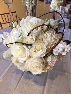 Cylinder arranged with white hydrangea, Pola Star roses, white stock, and white lisianthus accented with grape vine.  DorisTheFloristt.com