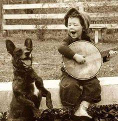 A young boy playing his banjo with his best friend!