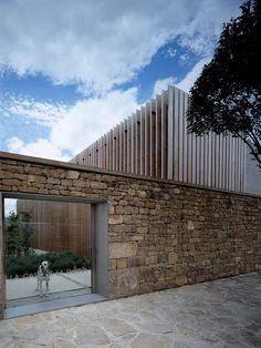 Muro residencial com pedra e vidro