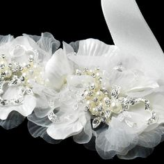 """This ivory colored bridal headband features two coupling flowers that are stationed along this 95"""" long ribbon. Dainty pearls and sparkling rhinestones accentuate the center portion of each flower along a lustrous detailing of silver plating metal. This accessory is very unique in the sense that it can be used as a headpiece with the flowers accented off to one side of the head or tied around the waste to add an extra glistening feature to your wedding or bridesmaid gown! #timelesstreasure"""