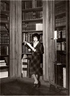 """Anita Loos reading in library.    The woman who penned the famous line, """"Kissing your hand may make you feel very very good but a diamond and safire bracelet lasts forever,"""" received her first diamond from her uncle Horace when she was seven years old. She never accepted another: """"therein lay my tragedy…I was a girl who would always pass up a diamond for a laugh."""""""