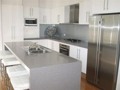 Modern Williams Designer Homes Kitchen. Grey white neutral colors. Ceaser Stone bench waterfall edges.