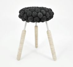 Hanna Bramford has taken the wool from one sheared sheep then carded, treated, and felted it into 100 balls to create the seat of a stool.  furniture, seating, lathe, turned legs, black sheep, handmade, contemporary, modern, conceptual, craft, artisan, fiber art, felting, natural materials, organic, layered, tradition, process, blog post