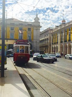 Trams driving through Lisbon, Portugal. Read more about what to do in Lisbon on http://passportandplates.com!