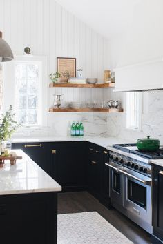 Mid-sized transitional l-shaped medium tone wood floor and brown floor kitchen photo in Chicago with a farmhouse sink, shaker cabinets, black cabinets, marble countertops, white backsplash, marble backsplash, paneled appliances and an island #kitchen #transitional