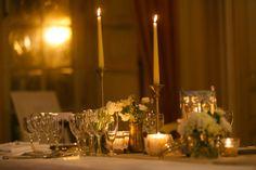des petits bouquets blanc dans des vases bas, et des chandelles très hautes dans de beaux chandeliers (à voir si on trouve des beaux chandeliers) avec qq bougies plus basses : bel effet