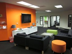 Commercial Office relocation using mostly IKEA furnishings and orange & lime green accents.  Karlstad sofa w/ gray tufted felt, Torsby white lacquer credenzas.  Ottomans from Steelcase.  Coffee table from CB2.
