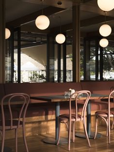 Lockhart had Michael Thonet Era Chairs custom colored in Clay, a shade from her own paint collaboration with Drikolor. The upholstered seat pads are done in Sunbrella Tresco Brick to match the banquettes. #restaurantdesign