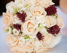 Bridal Bouquet of Blush Vendela Roses, Ivory Renunculus, white Lilac and Lilly of the Valley with Skimmia at Northbrook Park by Fiona Curry Flowers.