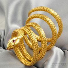 Antique Gold Snake Bracelet, the naturalistic head set with a synthetic ruby, joined to a coiling body of woven gold, 24.2 dwt. Victorian or Victorian style.