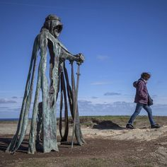 A woman passes the new 'Gallos' sculpture that has been erected at Tintagel Castle in Cornwall Britain on April 28th 2016. Both the castle managed by English Heritage and the nearby town of Tintagel have long been associated with the legend of King Arthur and continue to attract large visitor numbers. However efforts by English Heritage to update the visitor experience with the Gallos sculpture along with a rock carving of Merlin's face have met with criticism from some Cornish nationalists…
