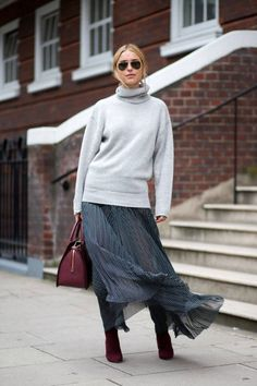 Layer an oversized sweater over a flowy skirt and boots for a stylish fall outfit