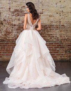 Look opulent in this ball gown with a Sabrina neckline, natural waistline, heavily adorned bodice, illusion V-back, and dreamy layered skirt with horsehair trim.