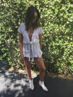 Stepping up our outfit game in a white ruffle romper, studded boots, and sunnies.