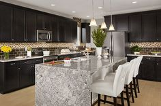A sleek stone island contrasts with dark cabinetry and tile. New homes in the Hacienda at Greer Ranch community by Gehan Homes. Surprise, AZ.