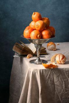 'Clementinen' von Nikolay Panov bei artflakes.com als Poster oder Kunstdruck $14.37  https://www.artflakes.com/de/products/clementinen-4 Obst-Stillleben mit vielen frischen Clementinen in Metall Vintage Vase und alten offenen Buch liegend auf dem Tisch auf tiefblauen Hintergrund