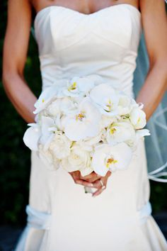 The bridal bouquet will be a clutch of cream hydrangeas, ivory garden roses, and white phalaenopsis orchids wrapped in ivory ribbon with the stems showing.