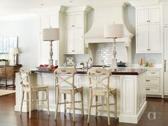 Beautiful kitchen features ivory shaker cabinets paired with white marble countertops.