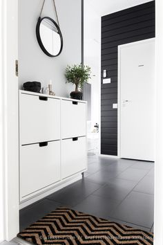 Black & white foyer and I recognize the shoe storage cabinet by Ikea.  Simple & clean. Grafiitinharmaassa kaksiossa