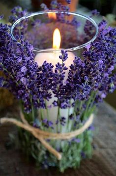 Purple Wedding Inspiration: This chic centerpiece is made from branches of lavender, tied around a glass candle holder with twine.