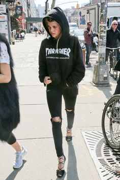 A black Thrasher hoodie, ripped jeans, and scrappy sandals