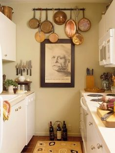 Much to like in this galley kitchen ... lots of sharp knives at hand, copper, art, thick wooden cutting board. They don't let having a small space slow them down!