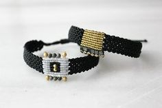 Black and gold wide macrame bracelet. A minimal, geometric design with classic colors to adorn your wrist all day round! Casual, rock, formal or beachwear, whatever the dress code is you can wear it with no second thoughts. And dont forget Christmas is around the corner, it would be a great gift for your friends and the perfect stocking stuffer. *Details Black and gold waxed cord hand knotted using micro macrame techniques with square hematite beads along one side of the gold section. The…