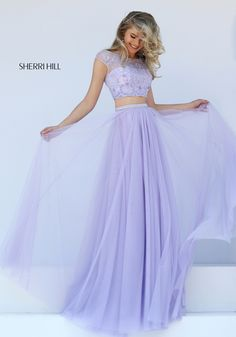 Gorgeously feminine and romantic, the Sherri Hill 50038 two-piece prom dress creates a timelessly classic A-line silhouette. The sweetheart crop top showcases a scalloped edged midriff and is overlaid with delicately beaded metallic lace, creating a wide illusion scoop neckline framed with cap sleeves. Illusion panels form a V on the back above a scalloped edged inverted V, creating a butterfly effect. A slim beaded band accentuates the waistline of the full-length skirt as it cascades in…