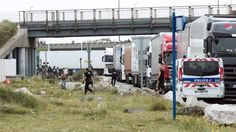 Policemen stand guard next to truck queuing to board a ferry to Britain. Read article: http://sharonslittlenewsblog.wordpress.com/2014/10/21/tear-gas-fired-at-calais-migrants/