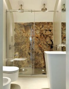 Un moderno cuarto de baño de estilo minimal, con una pared de piedra a contraste.