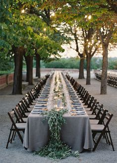 A long table is adorned with a living runner, accented by candlelight, creating a chic and sophisticated table guests are sure to love. wedding decorations, centerpieces, banquet tables