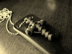 Paracord cross with ring tied with two-strand wall knots.