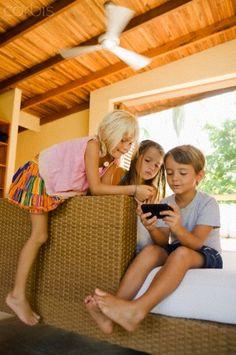 children playing indoors with cellphone games - 42-36262354 - Derechos protegidos - Fotografía de stock: Corbis
