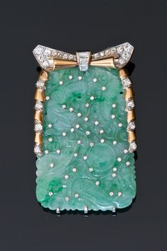 Art Deco brooch in gold and platinum formed from a plate engraved jade jadeite chisoise fighting a dragon studded with small diamonds.