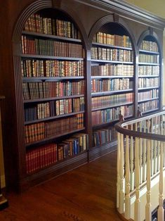 A hallway wall is turned into a home library after lined with a large bookcase in a traditional, formal style with an arched design